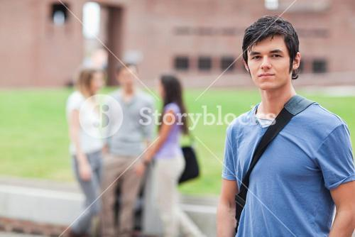 Handsome student posing while his classmates are talking