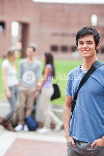 Portrait of a handsome student posing while his classmates are talking