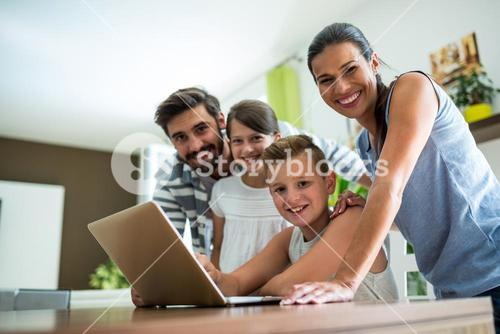 Portrait of happy family using laptop in the living room