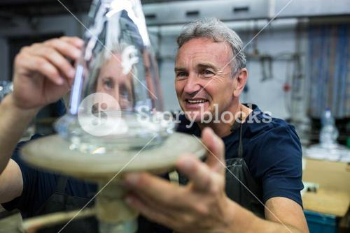 Glassblower and a colleague examining glassware