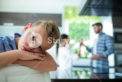 Sad boy leaning on chair while parents arguing in background