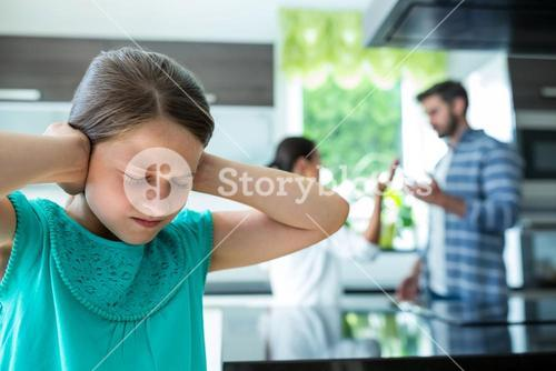 Sad girl covering her ears while parents arguing in background