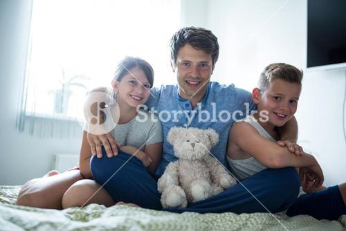 Portrait of father and kids sitting in bedroom