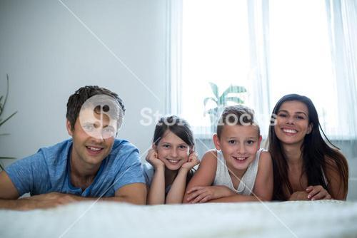 Portrait of parents and kids lying in bedroom