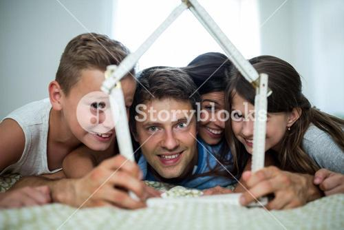 Happy family playing with model house in bedroom