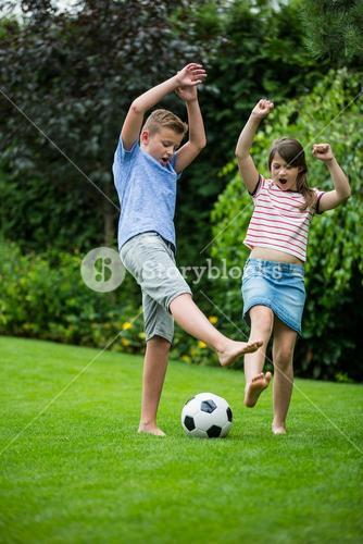 Kids playing with football in park