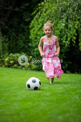Girl playing with football in park