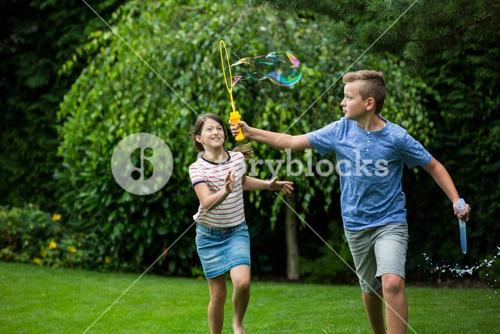 Kids playing with bubbles in the park