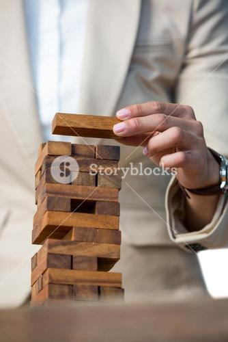 Businesswoman placing wooden block on a tower