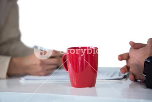 Businesswomen writing on clipboard with coffee mug on desk