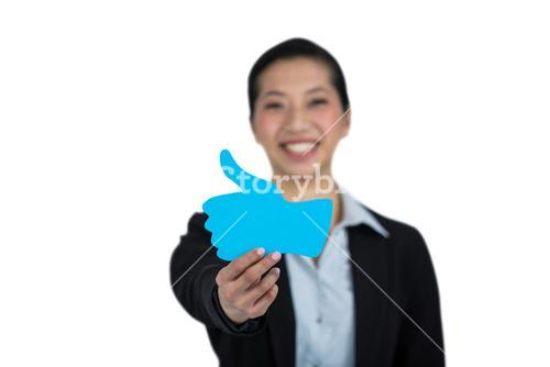 Portrait of businesswoman showing thumbs up sign board