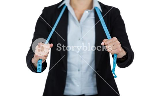 Businesswoman holding a measuring tape against white background