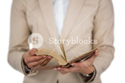 Mid section of Businesswoman flips through the pages of a book