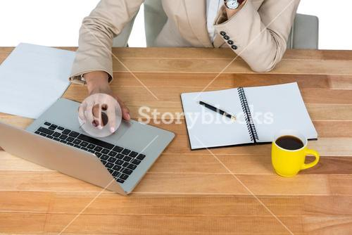 Businesswoman using laptop with diary and black coffee on table