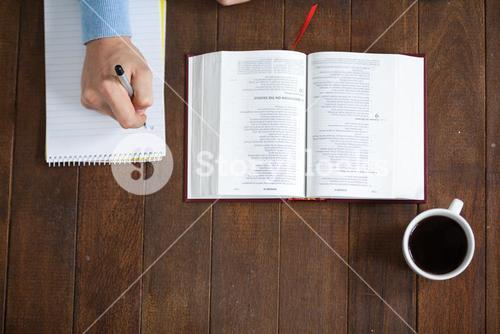 Man with a bible writing on notepad