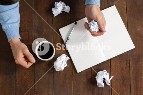 Man crumpling paper while having cup of coffee