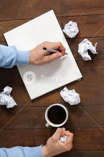 Man crumpling paper while writing on notepad