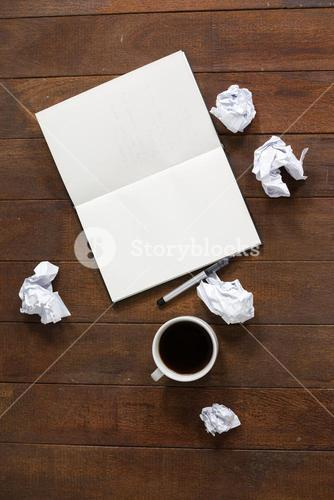 Notepad, pen, crumpled paper and cup of coffee