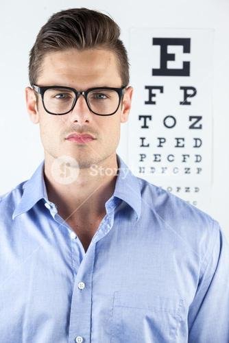 Man wearing spectacles with eye chart in background