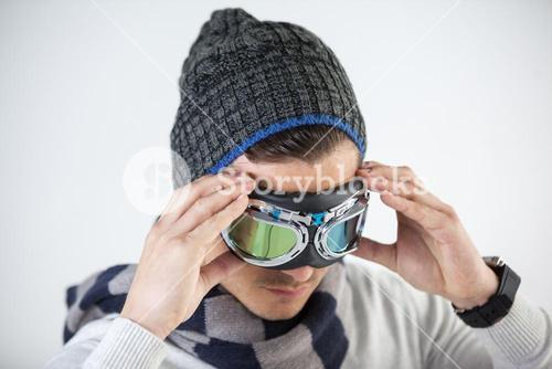 Man in winter clothing wearing aviator goggles