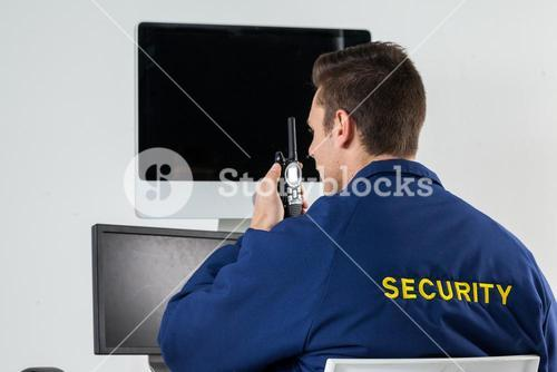 Security officer talking on walkie-talkie while looking at computer monitors