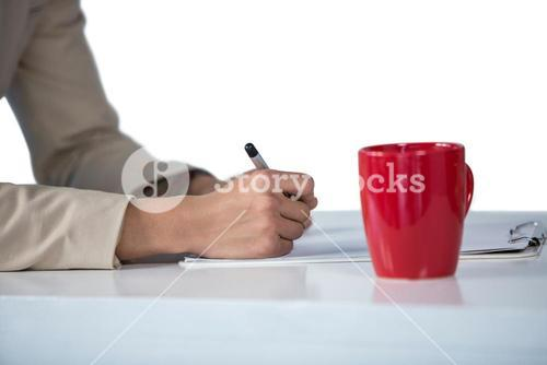 Businesswoman writing on clipboard with coffee mug on desk