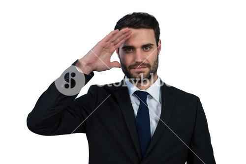 Businessman saluting against white background