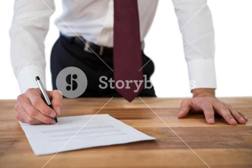 Businessman filling last will and testament form against white background