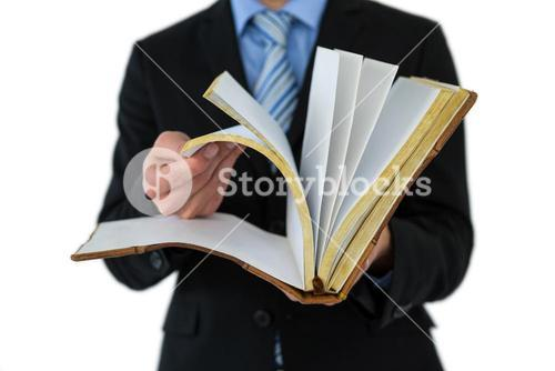 Mid section of businessman flips through the pages of a book