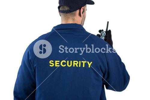 Rear view of security officer talking on walkie-talkie