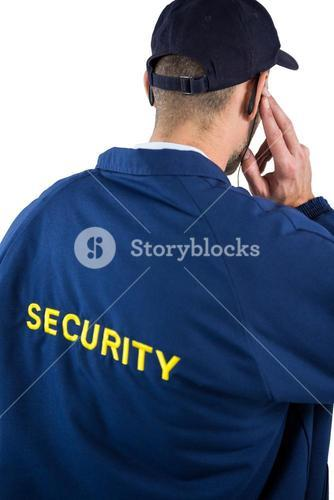 Rear view of security officer listening to earpiece