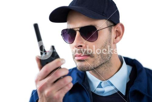 Handsome security officer talking on walkie-talkie