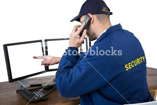Security officer talking on phone while pointing at computer monitors