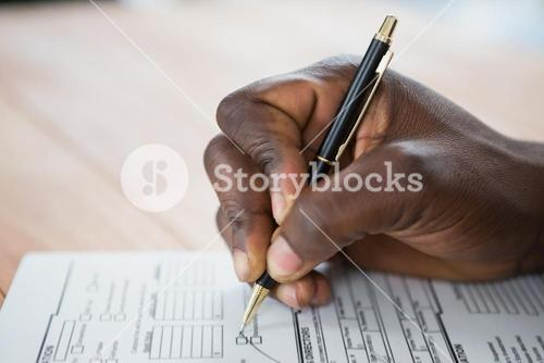 Hands of a man signing document