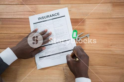 Hands of a man signing insurance document