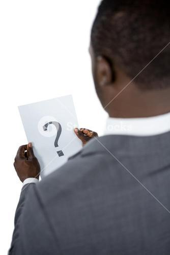 Rear view of businessman holding a question mark sign