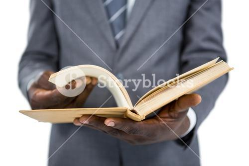 Mid section of businessman flipping the pages of a book