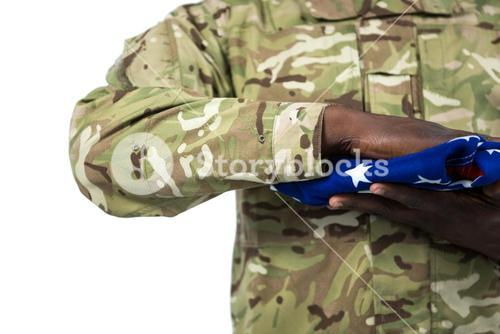 Mid section of soldier holding an american flag