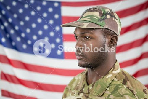 Soldier standing against american flag