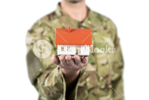 Mid section of soldier holding a model home