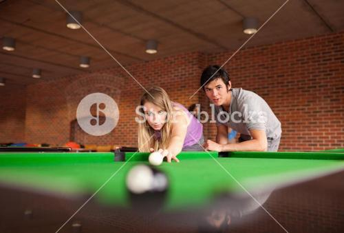 Man teaching pool to his girlfriend