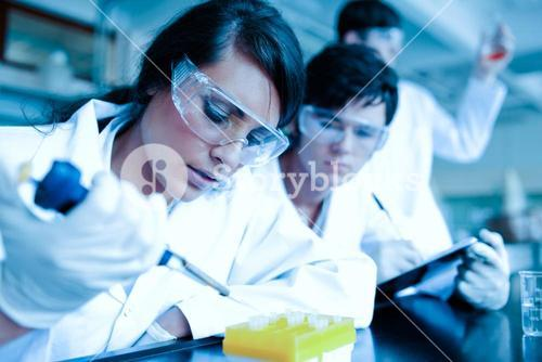 Young scientist dropping liquid in test tubes while her partner is taking notes