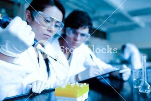 Cute scientist dropping liquid in test tubes while her partner is taking notes