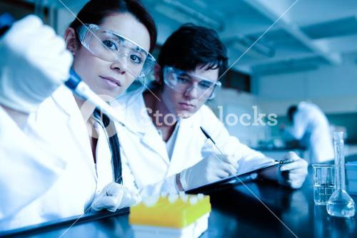 Science student dropping liquid in test tubes while her partner is taking notes