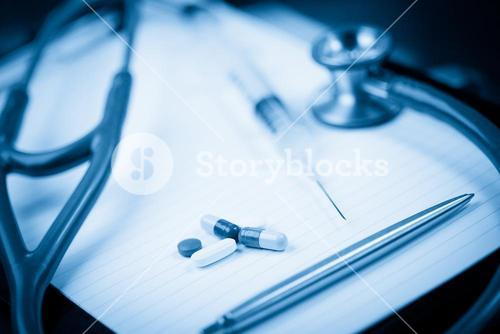 Note pad with stethoscope and pen along with serynge and capsules