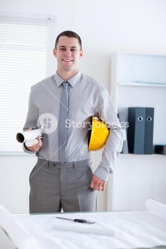 Architect carrying plans and helm