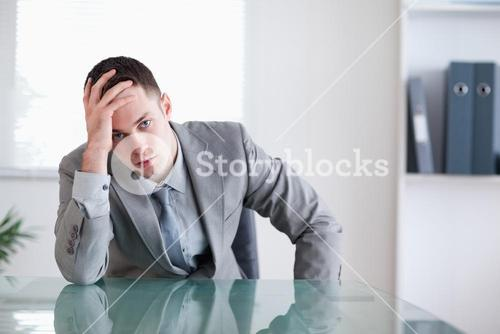 Disappointed businessman sitting behind a table