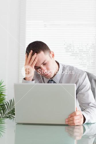 Close up of disappointed businessman looking at his laptop