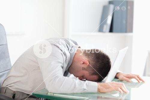 Overworked businessman taking a nap on his laptop