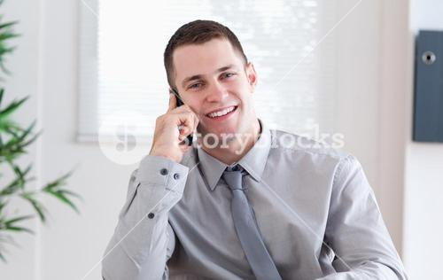 Businessman getting pleasant news on the mobile phone